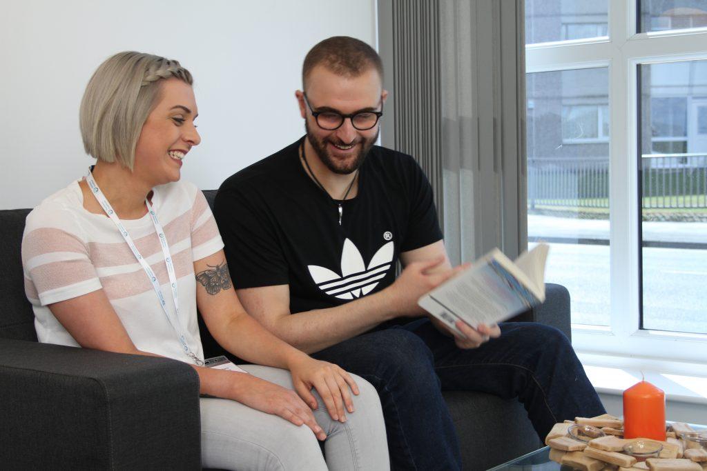 Resident and team member reading
