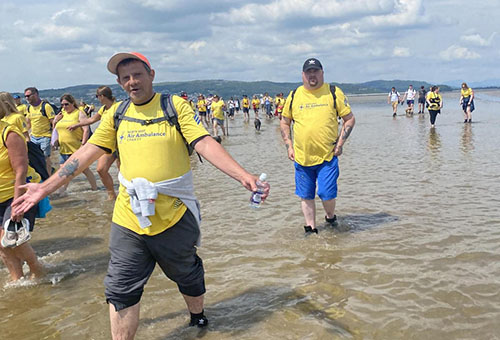 Glen Garth House staff and residents walk through shallow sea along the beach