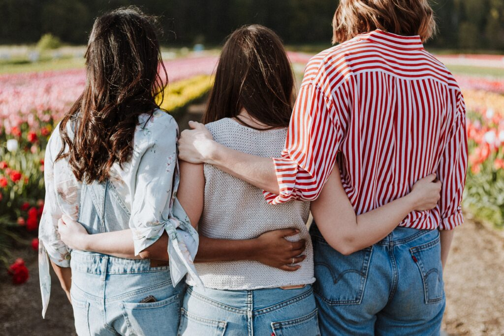 ADHD Awareness Month: 3 women hugging with their backs to camera